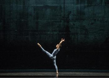 Dancer leaning back on one leg against a dark background