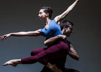 Image of two dancers over a dark background