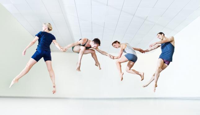 image of 4 dancers mid jump
